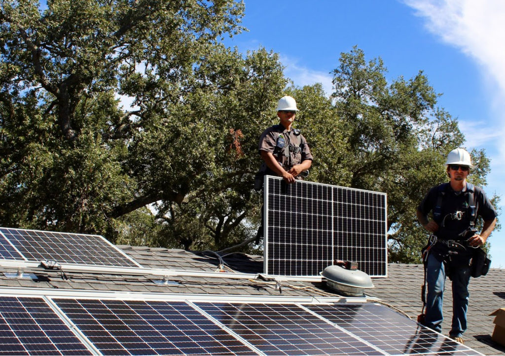 Job lead, Nick, with team on a rooftop solar install.